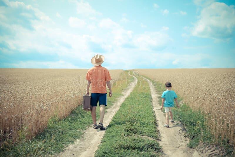 L'homme avec valize et garçon marchant sur la route entre photos libres de droits