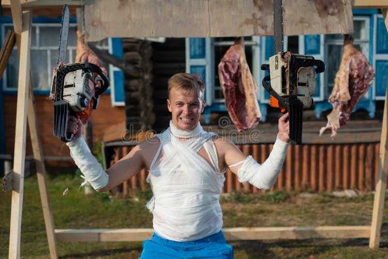 L'homme bandé crie terriblement, tenant deux tronçonneuses dans des ses mains sur le fond des carcasses de porc photos libres de droits