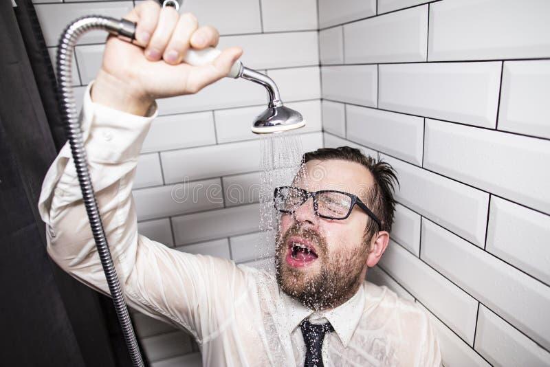 L'homme barbu avec des verres et des vêtements a fermé ses yeux et s'est penché contre le mur de la salle de bains, se versant ho photo libre de droits
