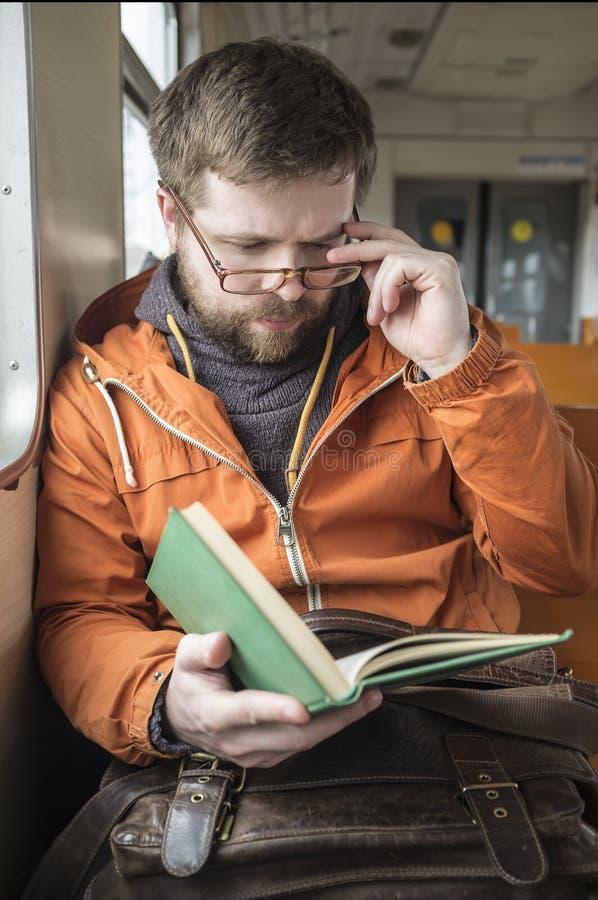 L'homme barbu avec des verres monte sur la maison de train du travail et du r image stock