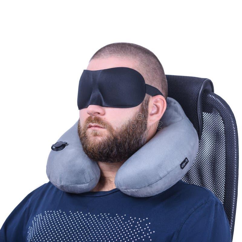 L'homme barbu avec le masque de sommeil et le voyage gris se reposent sur le fond blanc photographie stock