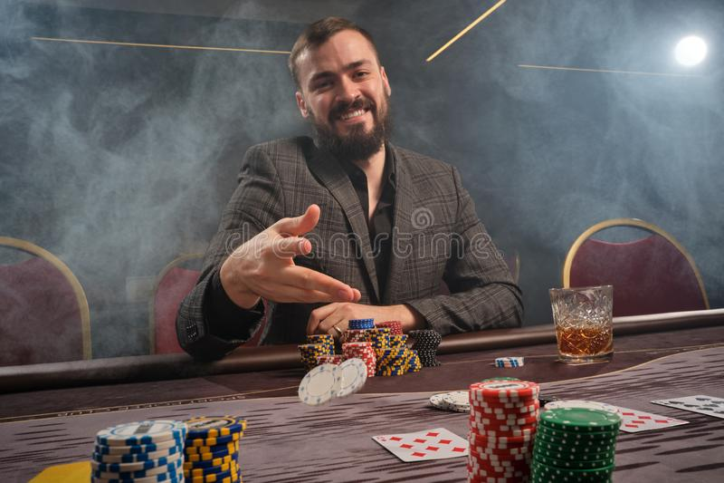 L'homme barbu bel joue au poker se reposant à la table dans le casino photos libres de droits