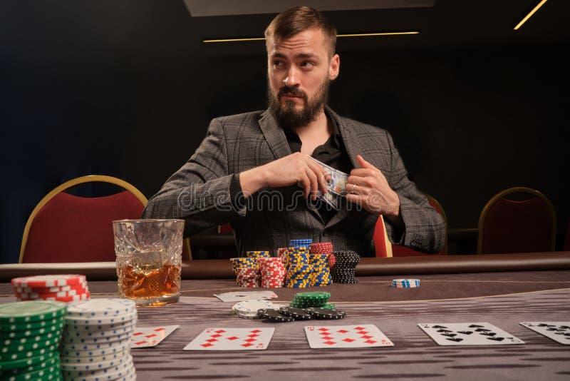L'homme barbu bel joue au poker se reposant à la table dans le casino photographie stock