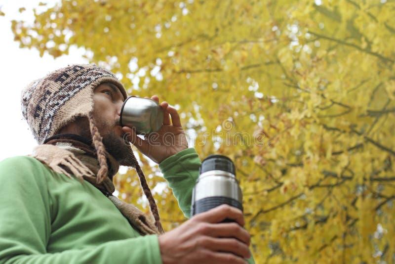 L'homme barbu dans le chapeau tricoté par laine boit du thé ou du café chaud de la tasse, la vue de côté inférieure, fond de feui photos stock