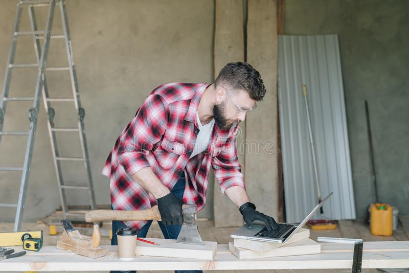 L'homme barbu de hippie est charpentier, le constructeur, supports de concepteur dans l'atelier, utilisant l'ordinateur portable  images stock