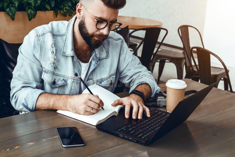 L'homme barbu de hippie s'assied à la table devant l'ordinateur portable et écrit dans le carnet, étudiant se prépare aux examens images libres de droits