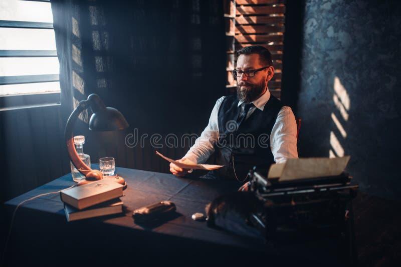 L'homme barbu en verres lit le texte manuscrit photo libre de droits
