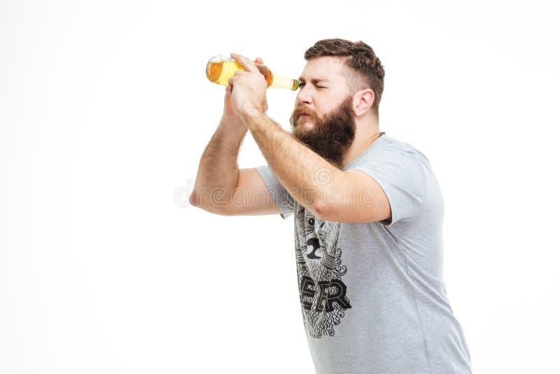 L'homme barbu espiègle tenant la bouteille de bière aiment le télescope photographie stock libre de droits