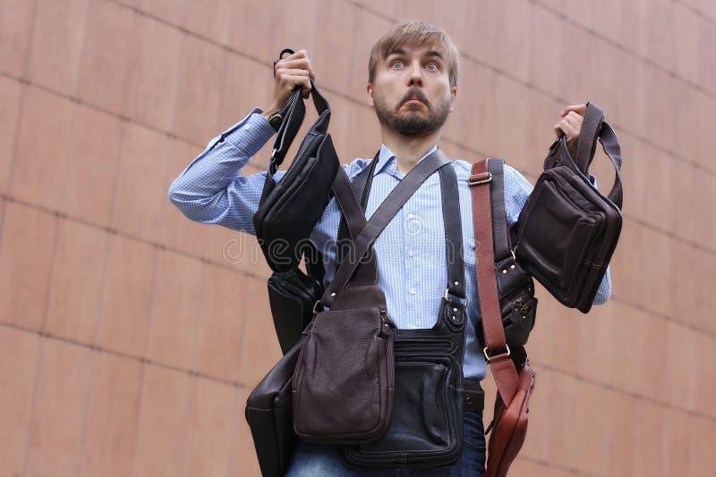 L'homme barbu est découragé par le choix du sac en cuir de l'homme photos libres de droits