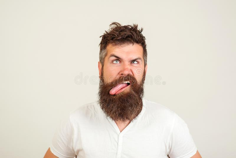 L'homme barbu fol montre sa langue, sur le fond blanc Expression négative de visage, émotion humaine, langage du corps, réaction  photo stock