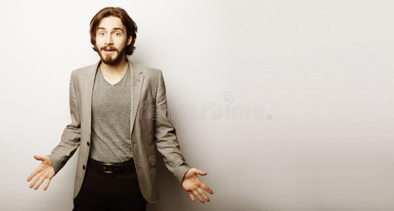 L'homme barbu voit quelque chose incroyable qui le fait heureux et excité, fait des gestes activement, exprime le choc agréable photo stock