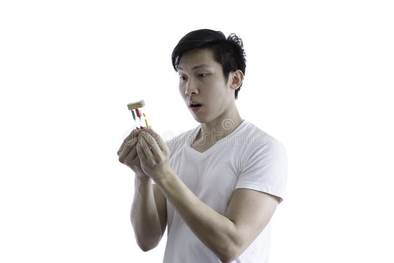 L'homme bel asiatique avec la chemise blanche et les lunettes oranges a SH photo stock