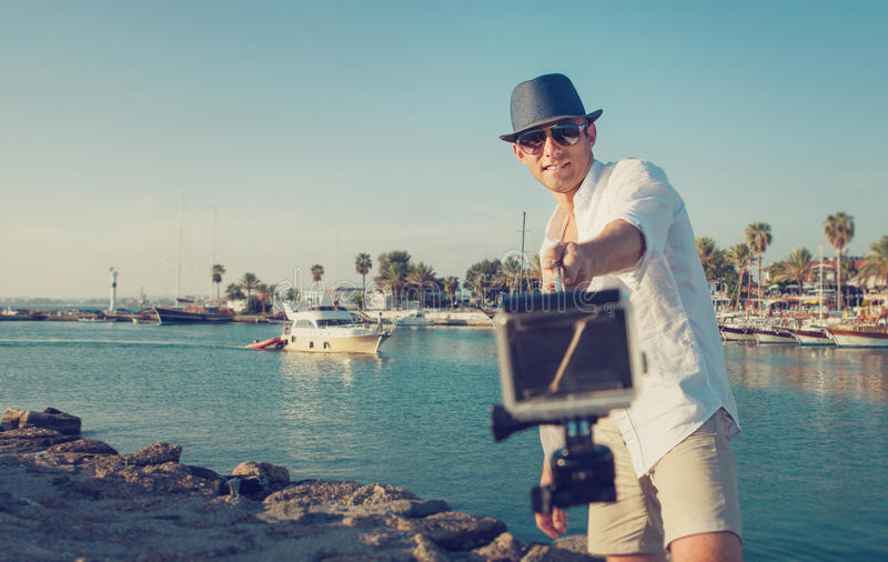 L'homme bel avec l'appareil-photo d'action prennent une photo de selfie dans le tropi photos libres de droits