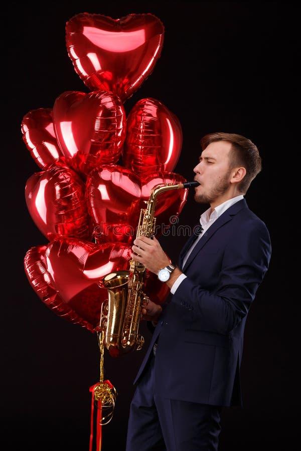 L'homme bel avec un rouge monte en ballon sur un fond noir Concept de Saint Valentin photographie stock libre de droits