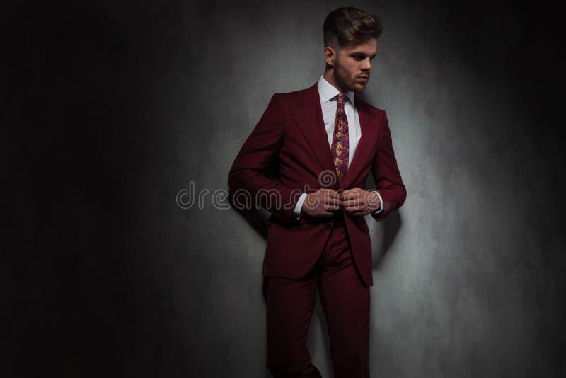 L'homme bel décontracté boutonnant son costume rouge regarde pour dégrossir photographie stock