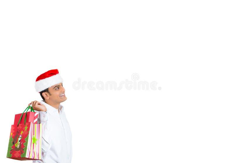 L'homme bel dans le chapeau rouge de Santa a perdu dans les pensées tenant le sac de fête images libres de droits