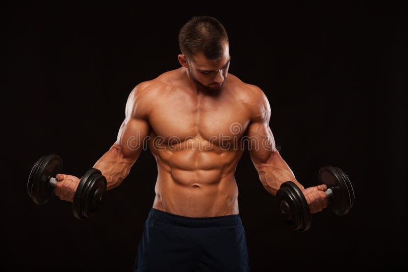 L'homme bel musculaire s'exerce avec des haltères dans le gymnase D'isolement sur le fond noir avec Copyspace photo libre de droits