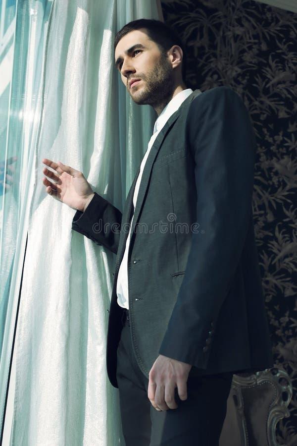 L'homme bel porte les vêtements élégants, posant dans la chambre à coucher photographie stock