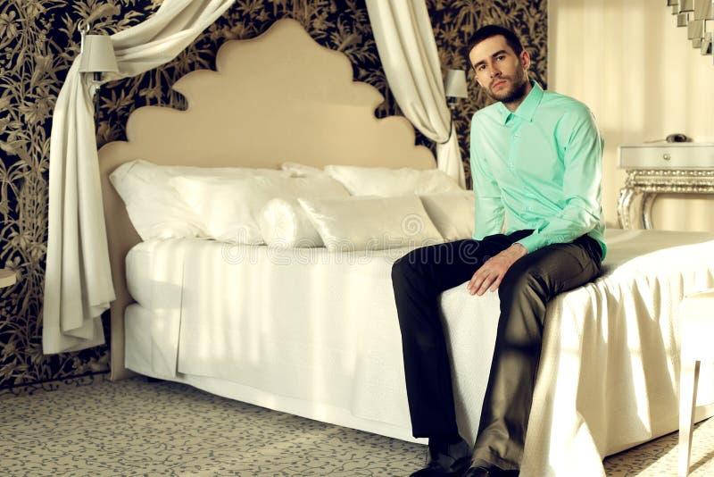 L'homme bel porte les vêtements élégants, posant dans la chambre à coucher image stock