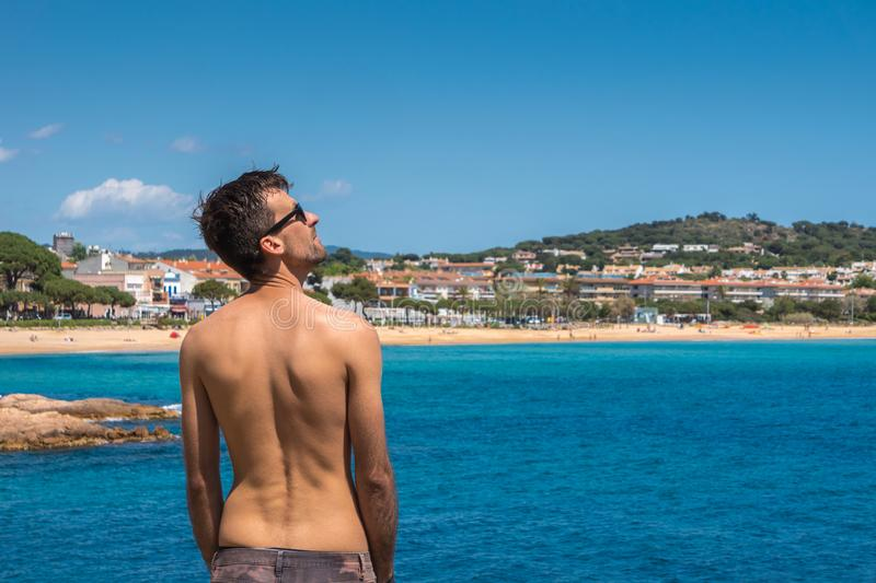 L'homme bel sur la plage en mer a tourn? de nouveau ? la cam?ra regardant le soleil, d?contract?, concept de vacances Palamos, Co photo libre de droits