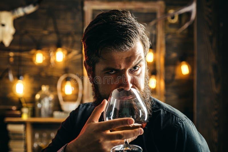 L'homme boit de l'eau-de-vie fine ou du whiskey Costume de port d'homme barbu et eau-de-vie fine ou cognac potable de whiskey Le  photographie stock