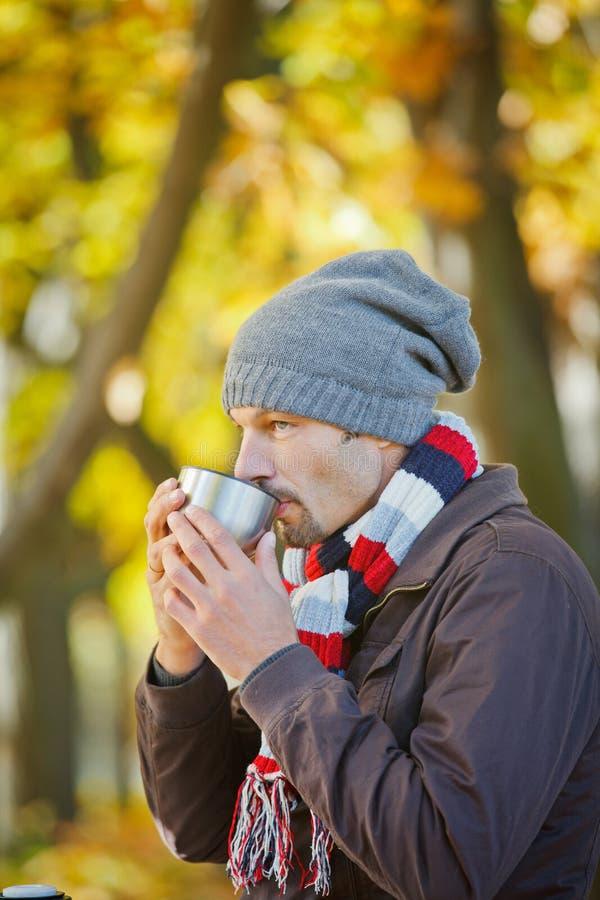 L'homme boit du thé en stationnement d'automne images libres de droits