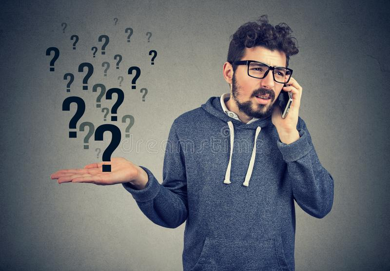 L'homme bouleversé parlant au téléphone portable a beaucoup de questions photo libre de droits