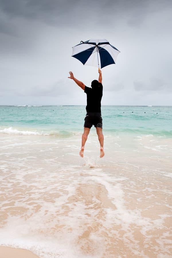 L'homme bronzé sautent avec le parapluie en mer bleue image libre de droits