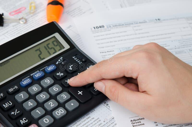 L'homme calcule l'impôt sur le revenu images stock