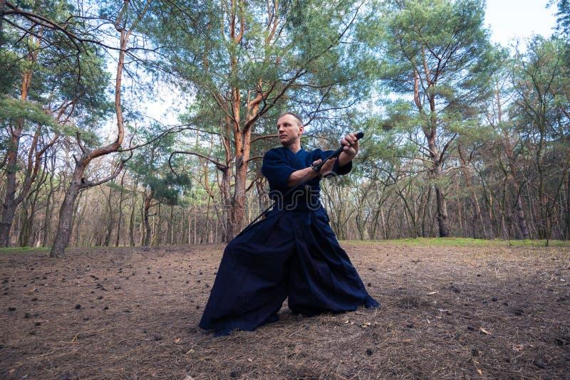 L'homme caucasien avec un katana pratique des arts martiaux photos stock