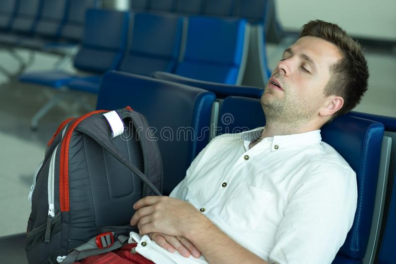 L'homme caucasien dort dans le secteur de salon à l'aéroport photos stock