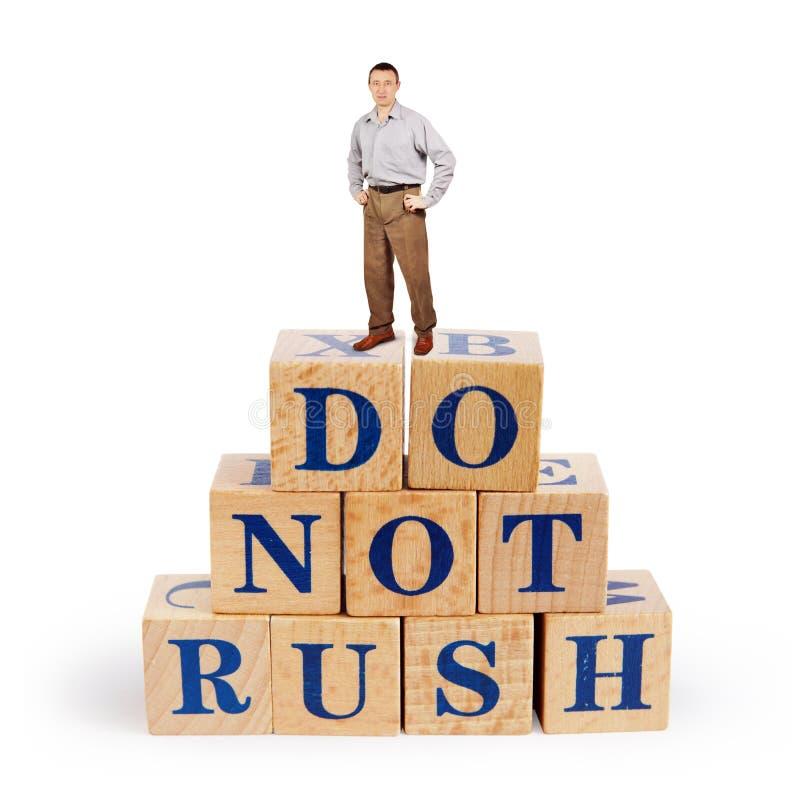 L'homme caucasien se tient sur un tas des blocs en bois avec un appel ne se précipitent pas photos stock