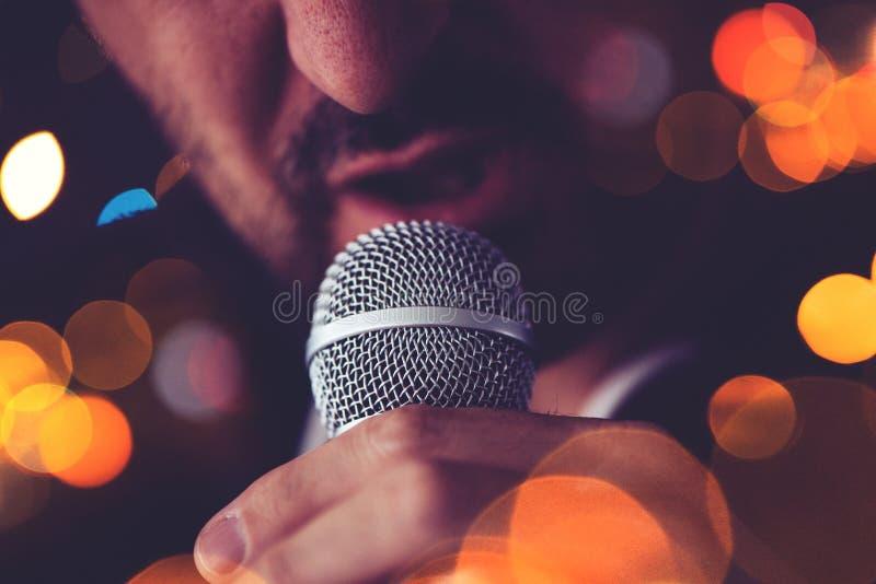 L'homme chante le karaoke dans une barre photos libres de droits