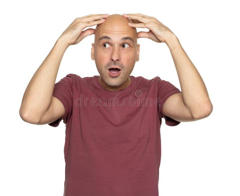 L'homme chauve étonné tient sa tête dans des mains photos libres de droits