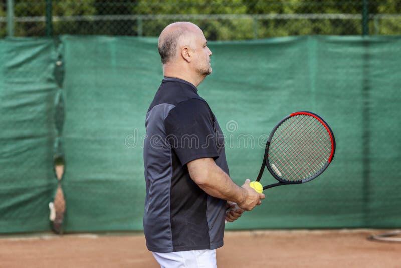 L'homme chauve adulte joue au tennis sur la cour Jour ensoleill? photos libres de droits
