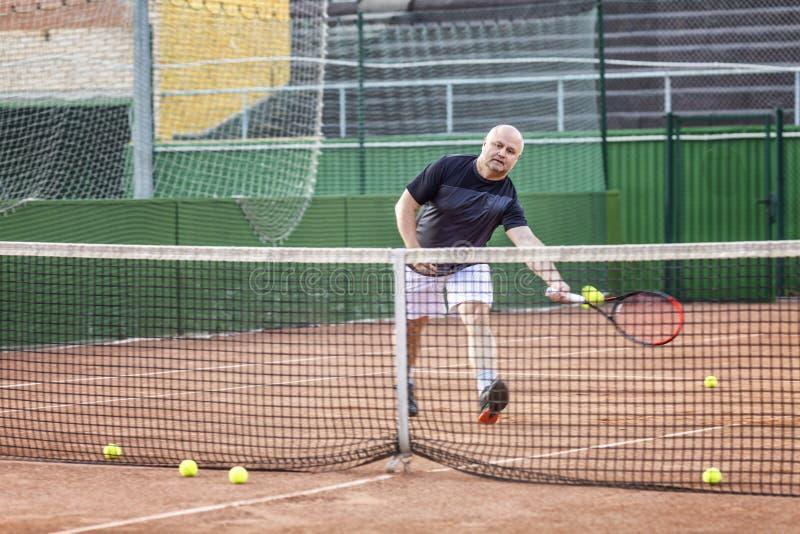 L'homme chauve adulte joue au tennis sur la cour Jour ensoleill? photos stock