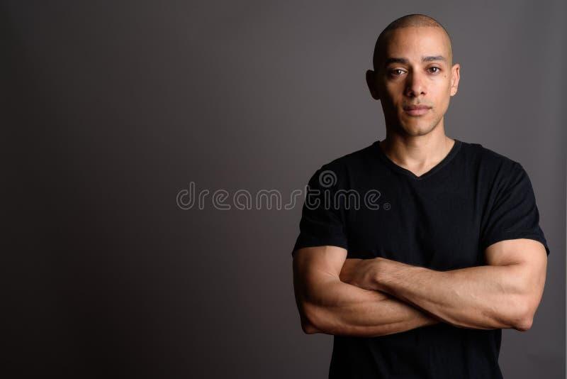 L'homme chauve bel utilisant la chemise noire avec des bras a croisé photo libre de droits