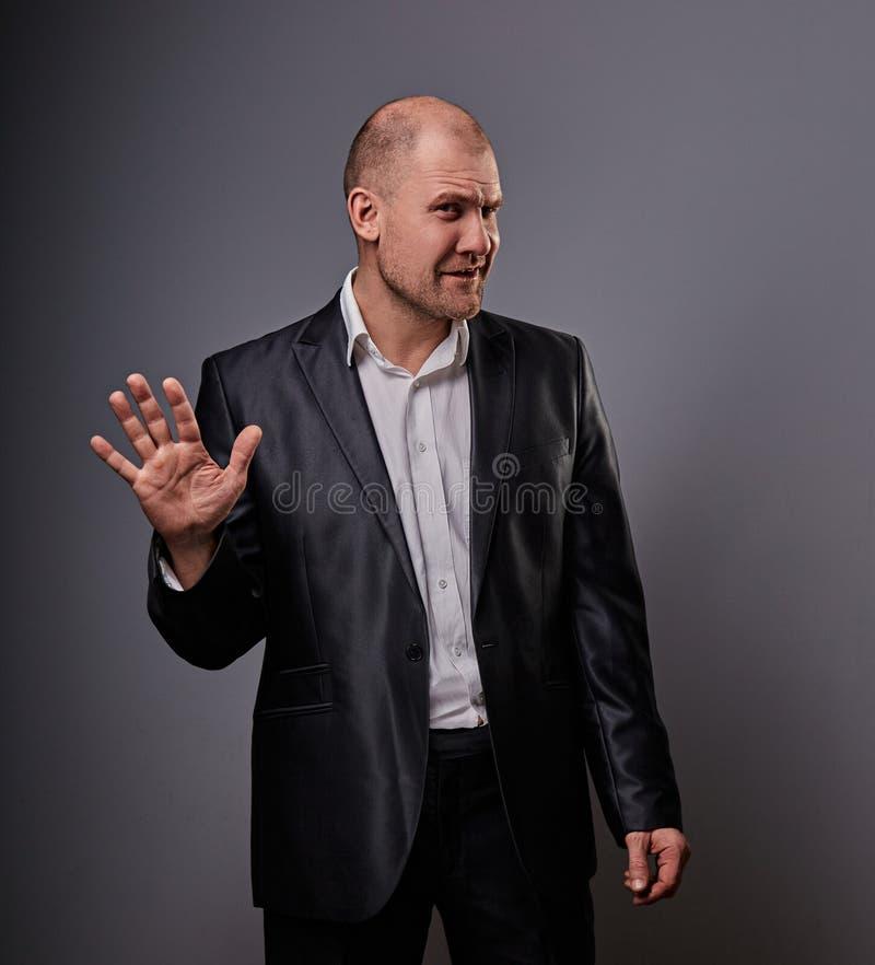 L'homme chauve déprimé malheureux de busuness dans le costume noir montrant la paume pour s'arrêter se connectent le fond gris cl photo libre de droits