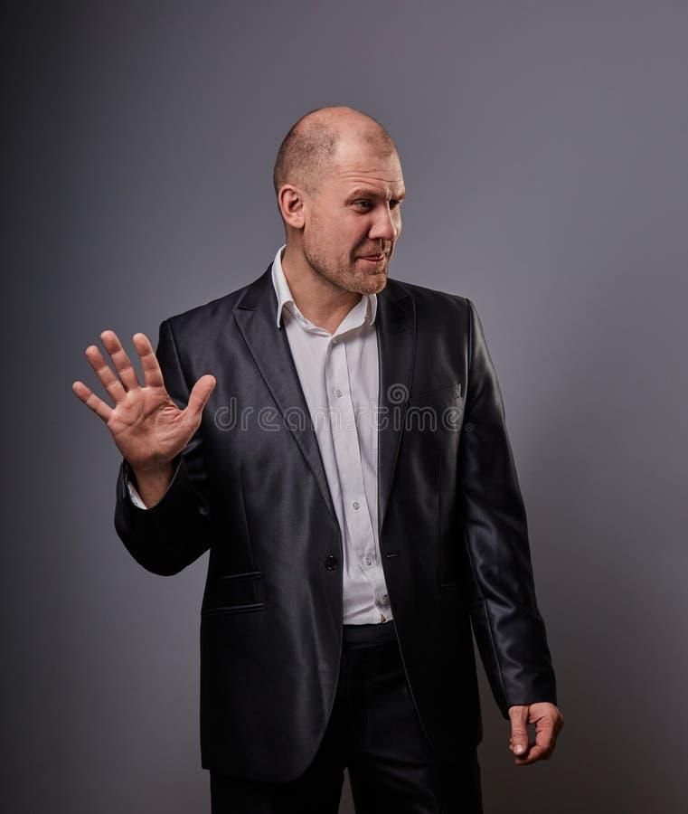 L'homme chauve déprimé malheureux de busuness dans le costume noir montrant la paume pour s'arrêter se connectent le fond gris cl photographie stock libre de droits