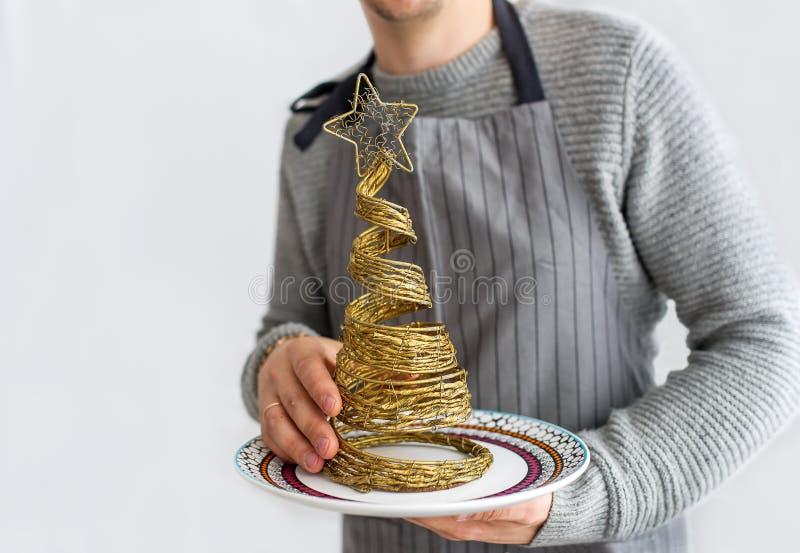 L'homme chauve dans un tablier juge un petit arbre de sapin décoratif de paille disponible images libres de droits