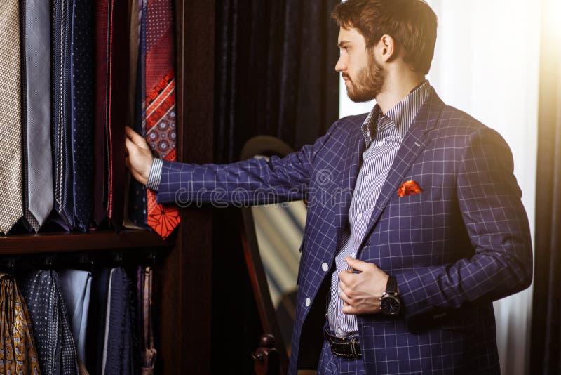L'homme choisissant la cravate pour assortir son costume dans le custume a fait la boutique de mode de vêtement image stock