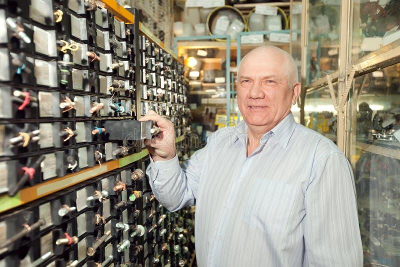 L'homme choisit des dispositifs de fixation dans la mémoire de pièces d'auto photos stock