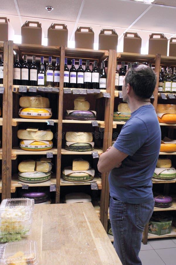 L'homme choisit le fromage photo stock