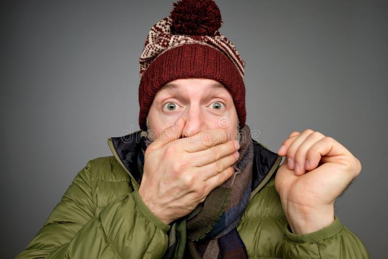 L'homme choqué gêné dans les vêtements et la bâche chauds d'écharpe disent du bout des lèvres avec des mains Il a entendu les pré photo libre de droits
