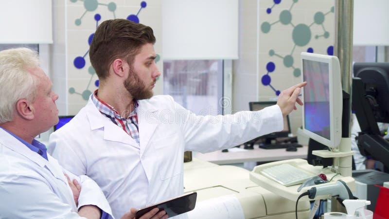 L'homme compare des données sur l'ordinateur et le comprimé au laboratoire images libres de droits