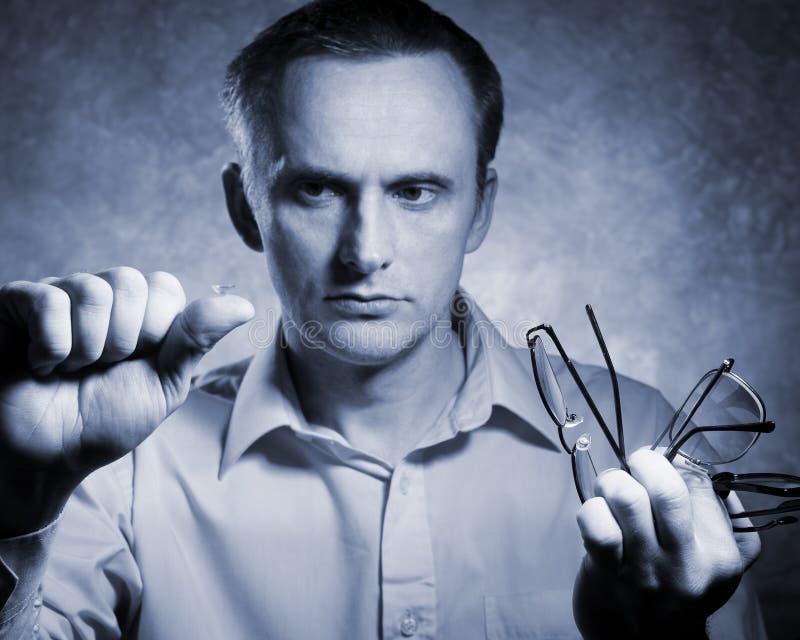 L'homme compare le lense de contact aux verres images libres de droits