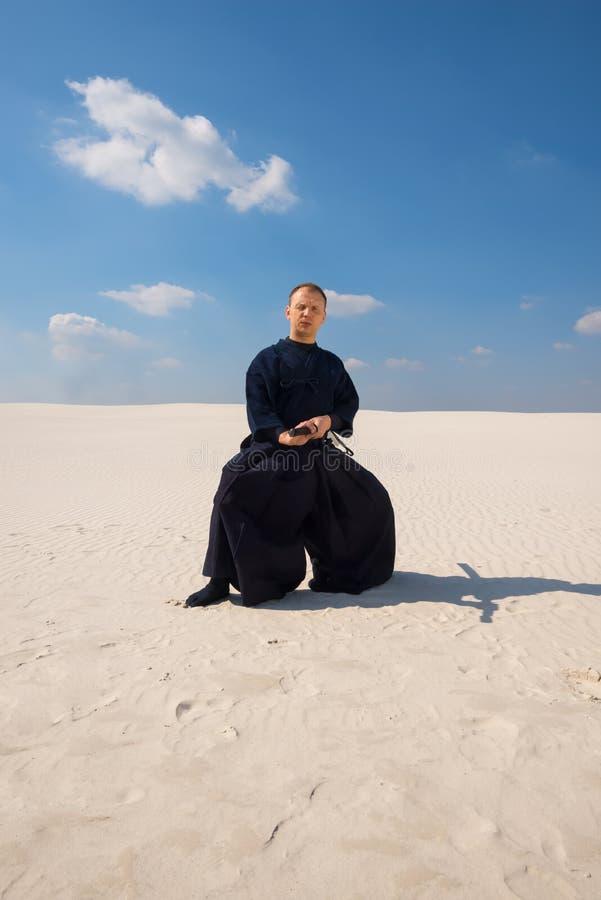 L'homme concentré pratique des arts martiaux dans un désert photographie stock libre de droits