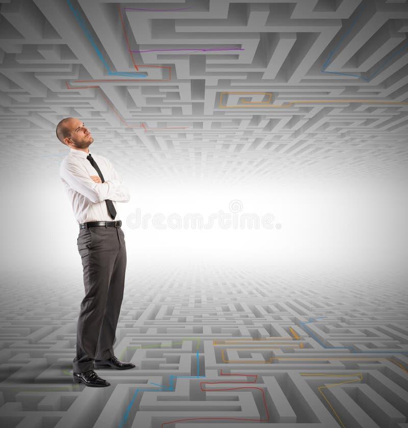 L'homme confus d'affaires cherche une solution au labyrinthe image stock
