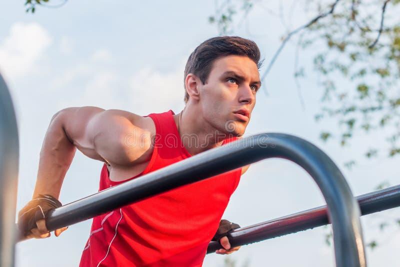 L'homme convenable faisant le triceps plonge sur des barres parallèles au parc s'exerçant dehors photographie stock