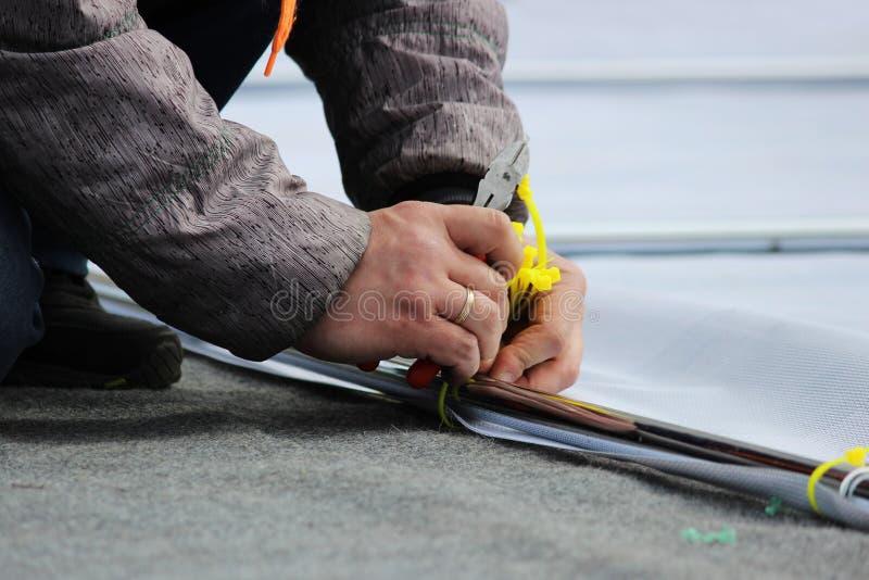 L'homme coupe les liens en plastique des brides avec les pinces des coupe-fil pendant le démontage de l'étape après le holi photographie stock libre de droits